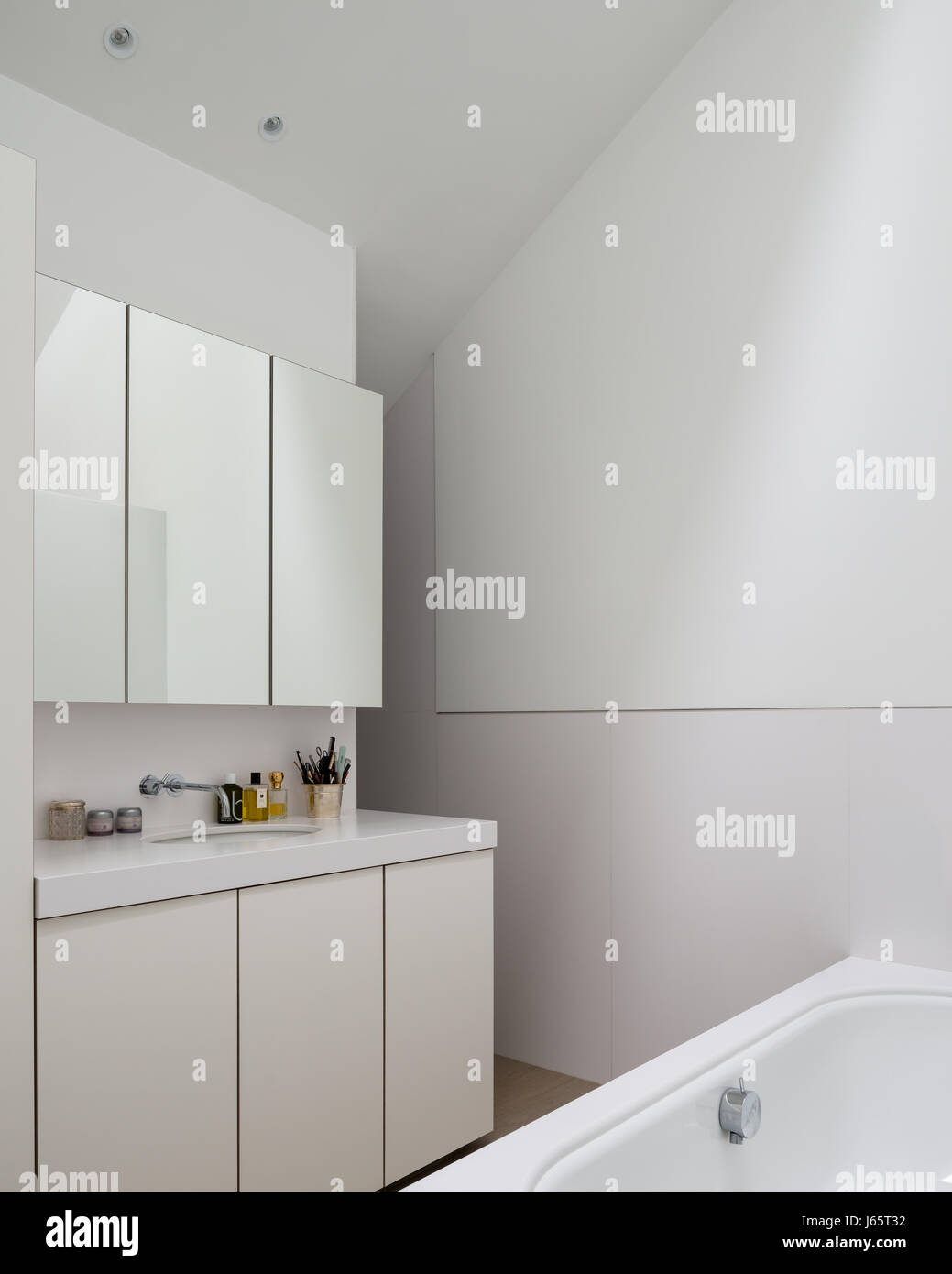 Mirrored cabinets above basin in pure white bathroom Stock Photo