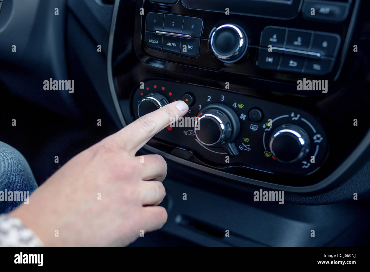 male hand pressing button in modern car. Man adjusts the temperature of the car air conditioner - Stock Image