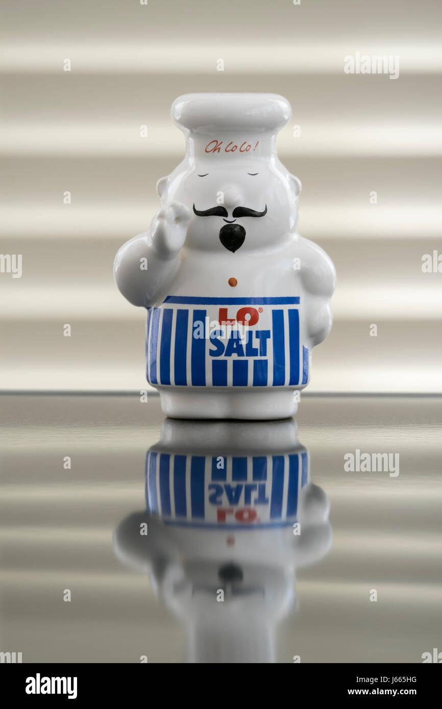 china salt cellar in the shape of a chef wearing a blue strioped apron with the words LO SALT written on it, LO - Stock Image