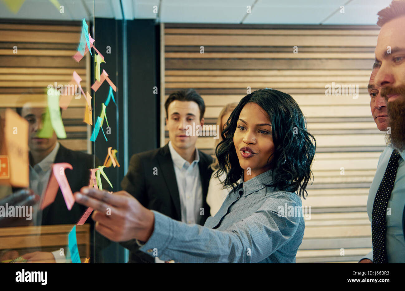Black business woman in front of mixed business team. Having a standing meeting brainstorming ideas using posters - Stock Image