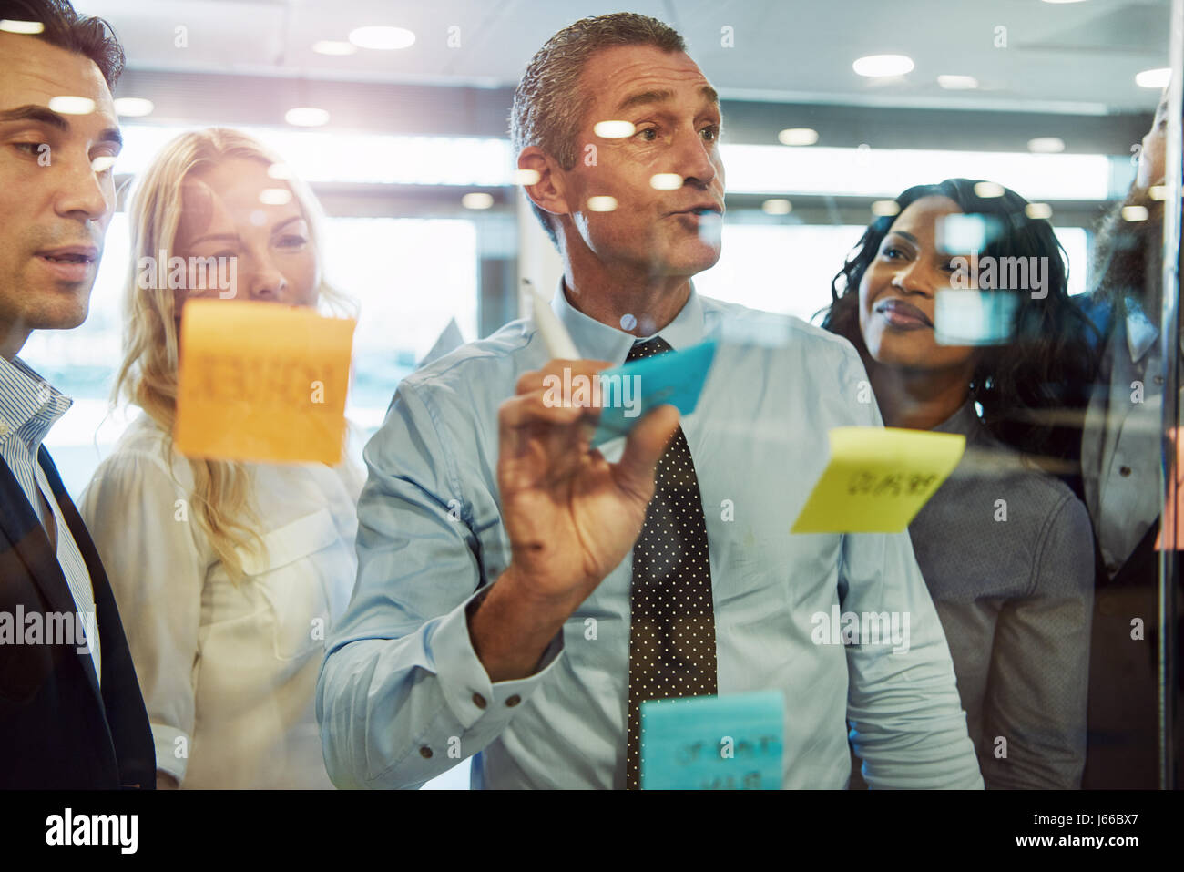 Half body portrait of business manager choosing sticky note on glass in office with colleagues in background, idea - Stock Image