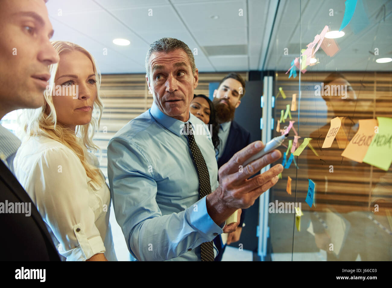 Businessman in a meeting with colleagues grouped around ideas on sticky memos looking aside with an attentive expression - Stock Image