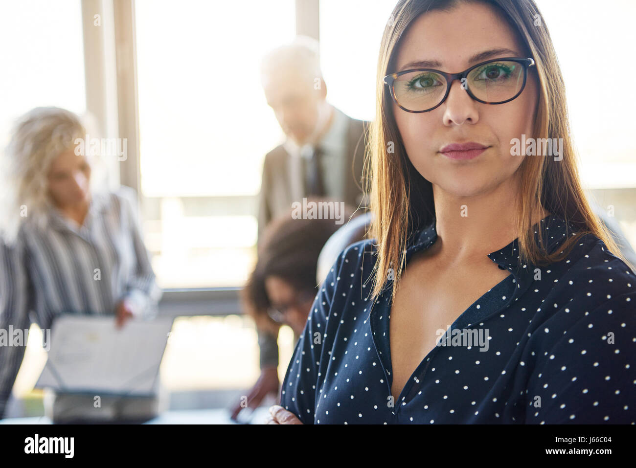Serious business woman in front of team in office, looking at camera - Stock Image