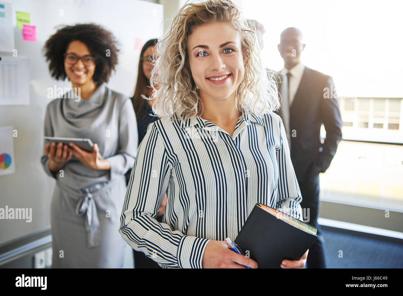 Business woman standing in front of colleagues, mixed races people looking positive - Stock Image