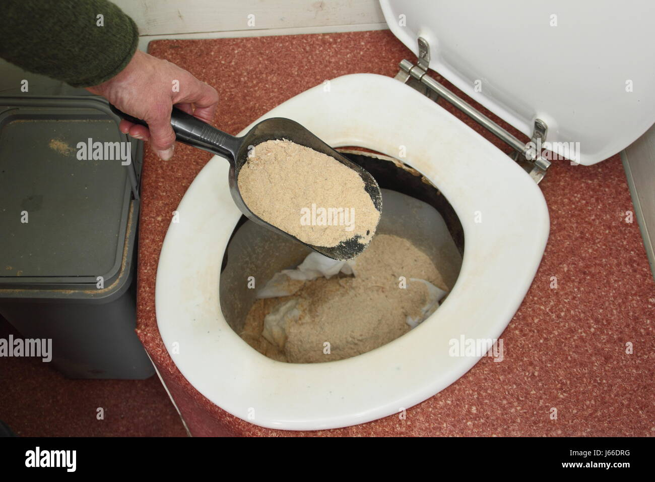 Sawdust is sprinkled into a working composting toilet