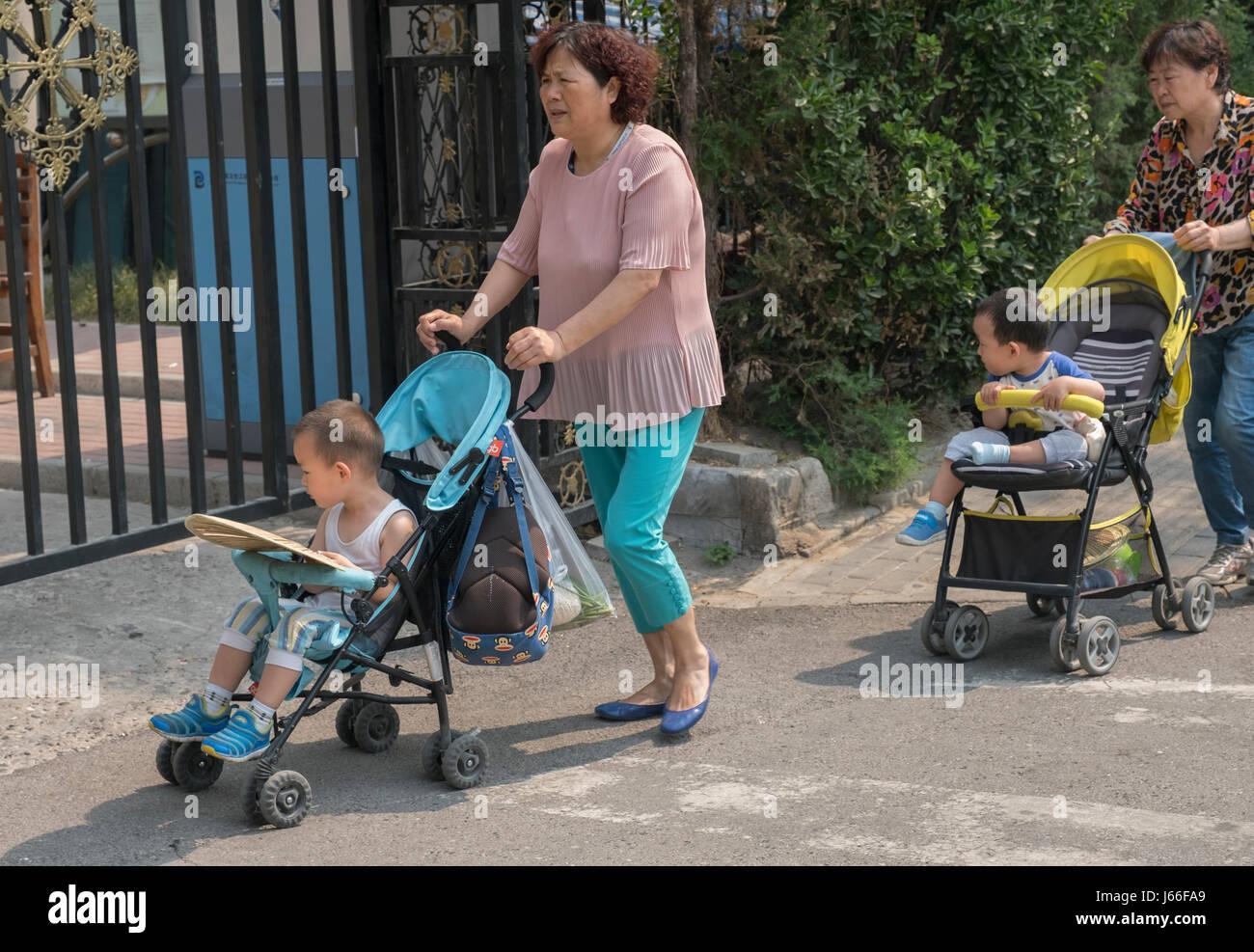 Grandmothers pushing grandchildren in buggies in Beijing, China. - Stock Image