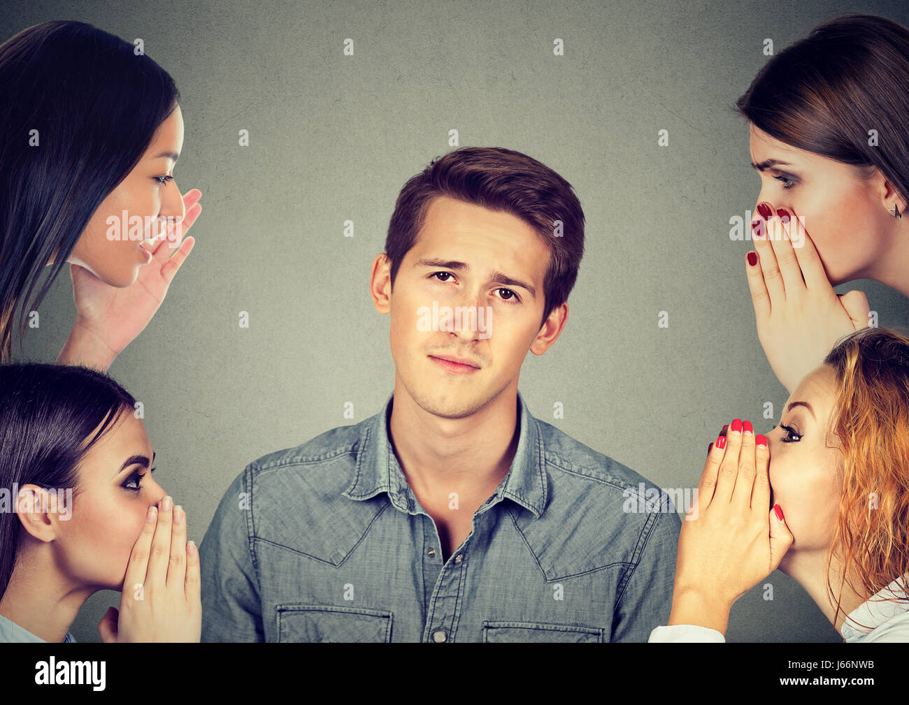 Four women whispering a secret latest gossip to a bored annoyed man - Stock Image