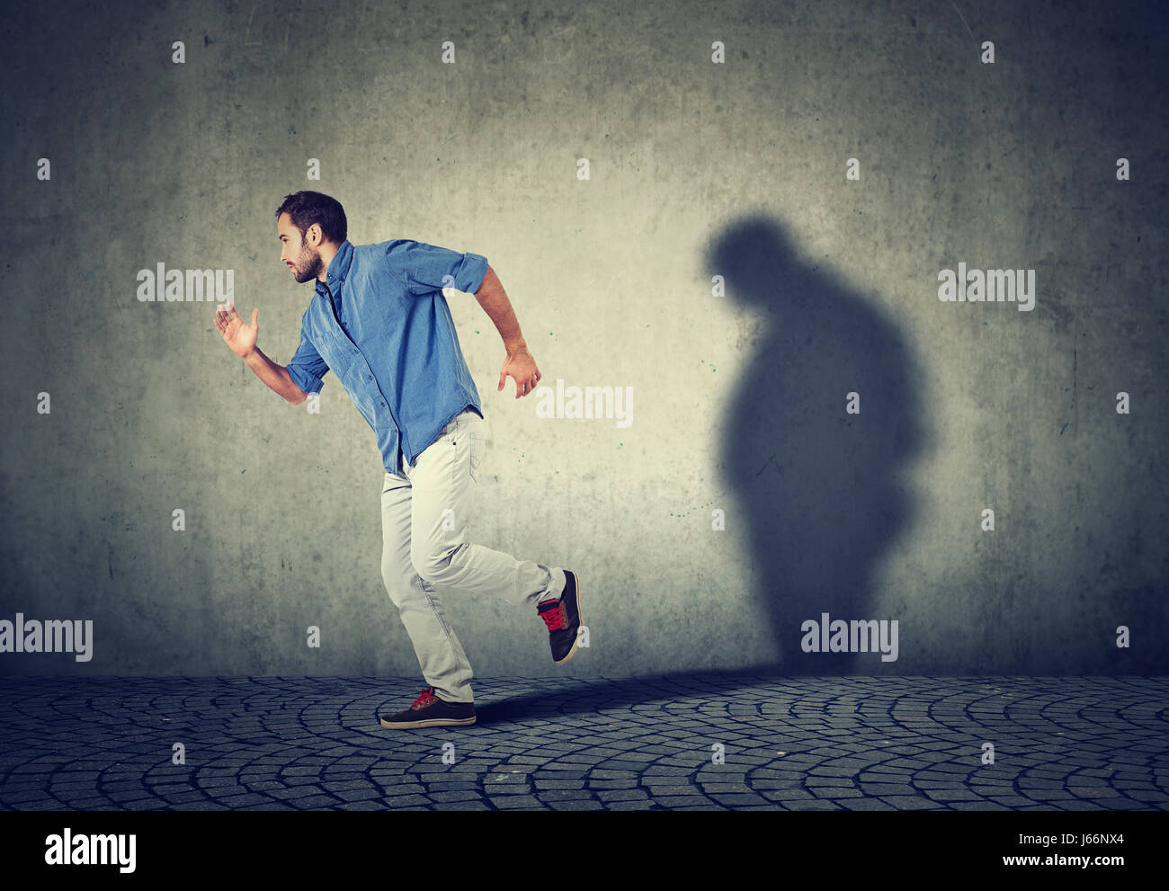 Man running away from his sad gloomy fat shadow on the wall. Mental health and body weight control concept - Stock Image