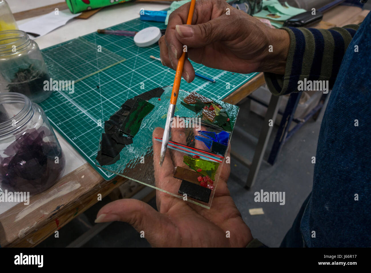 Person creating a glass fusion piece, decorating it using a paintbrush, UK - Stock Image