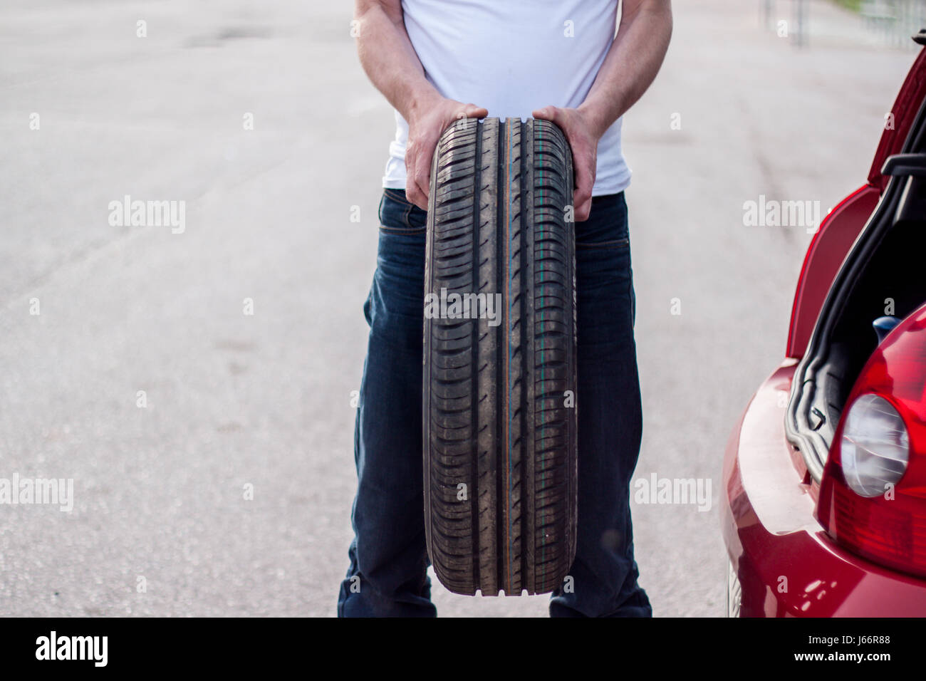 Car remained out of order on the road, the driver pulls the spare tire out of the trunk to be replaced - Stock Image