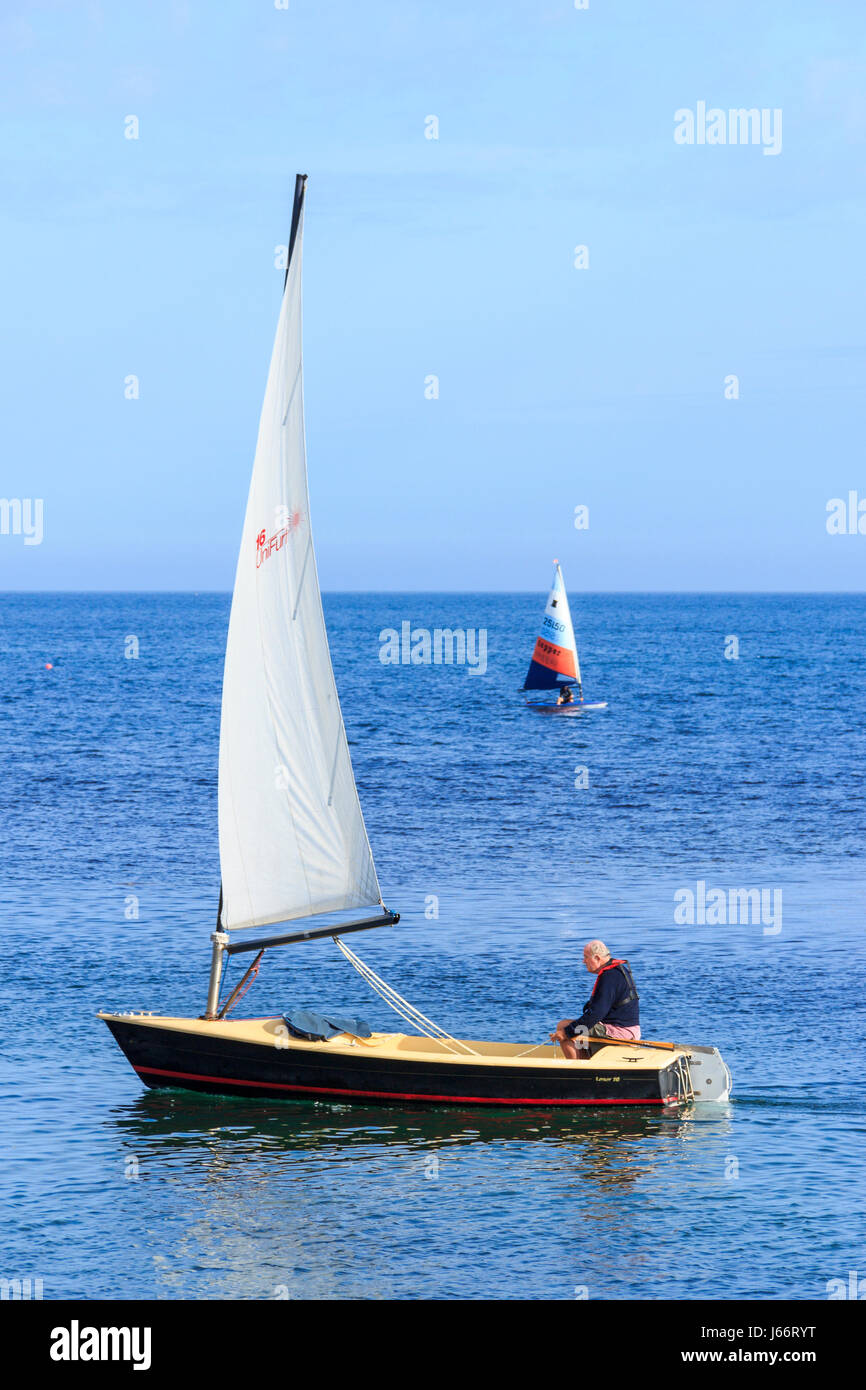 Two sailing dinghies on a calm blue sea at Ringstead Bay, Dorset, UK - Stock Image