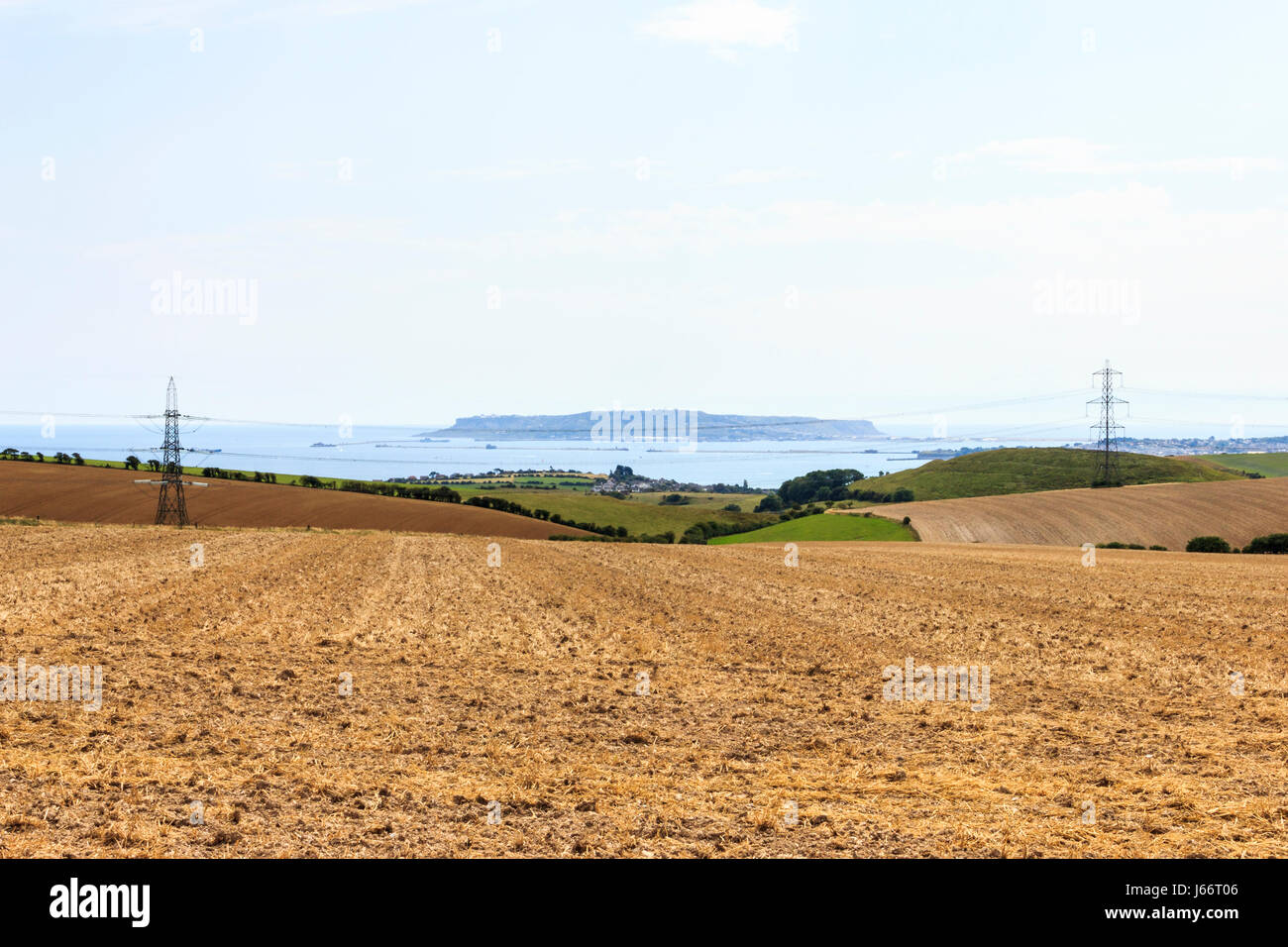 View across a harvested stubble crop field, the Isle of Portland in the distance, Dorset, UK Stock Photo