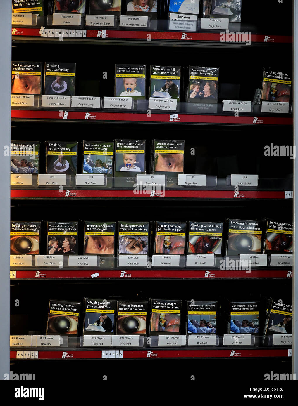 Cigarettes and tobacco for sale in a corner shop in Liverpool in standardised packaging bearing graphic warnings - Stock Image
