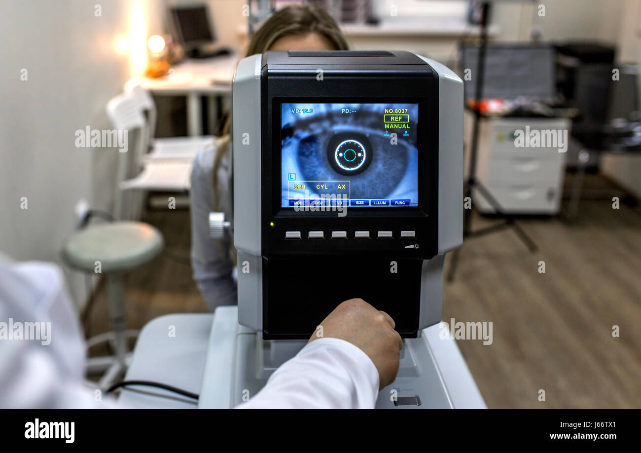 The Optical Instruments for examines the sight. optometrist examining female patient in ophthalmology clinic - Stock Image