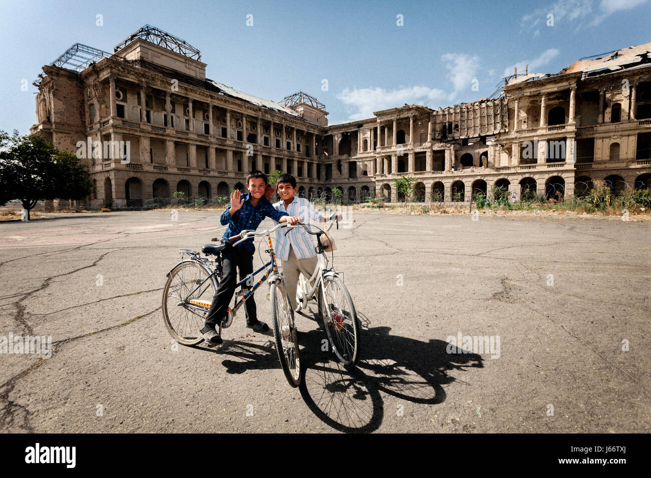 Boys ride their bikes around Darul Aman Royal Palace, Kabul, Afghanistan - Stock Image