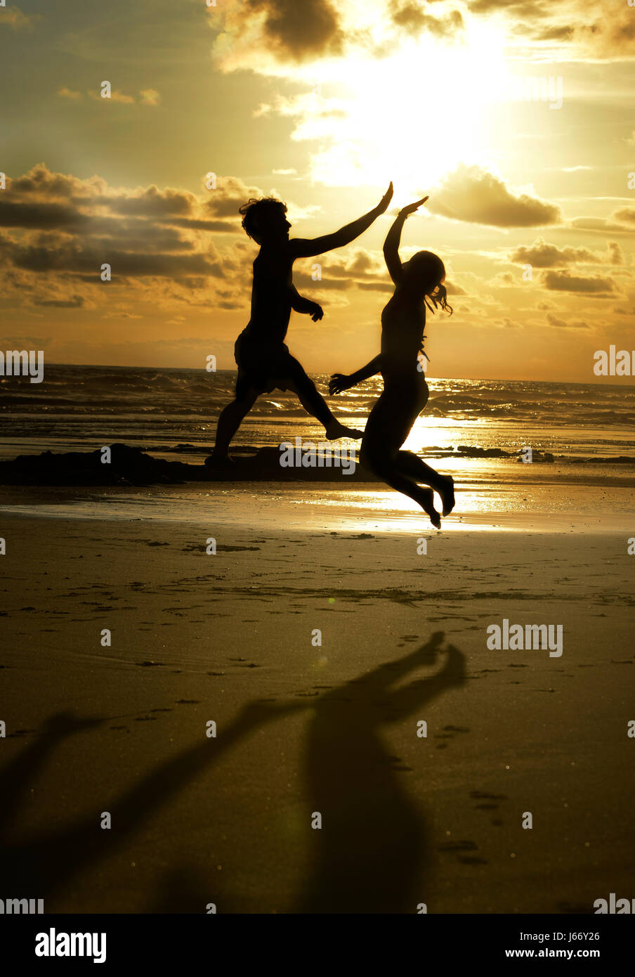 Friends high-five on a beach at sunset. - Stock Image