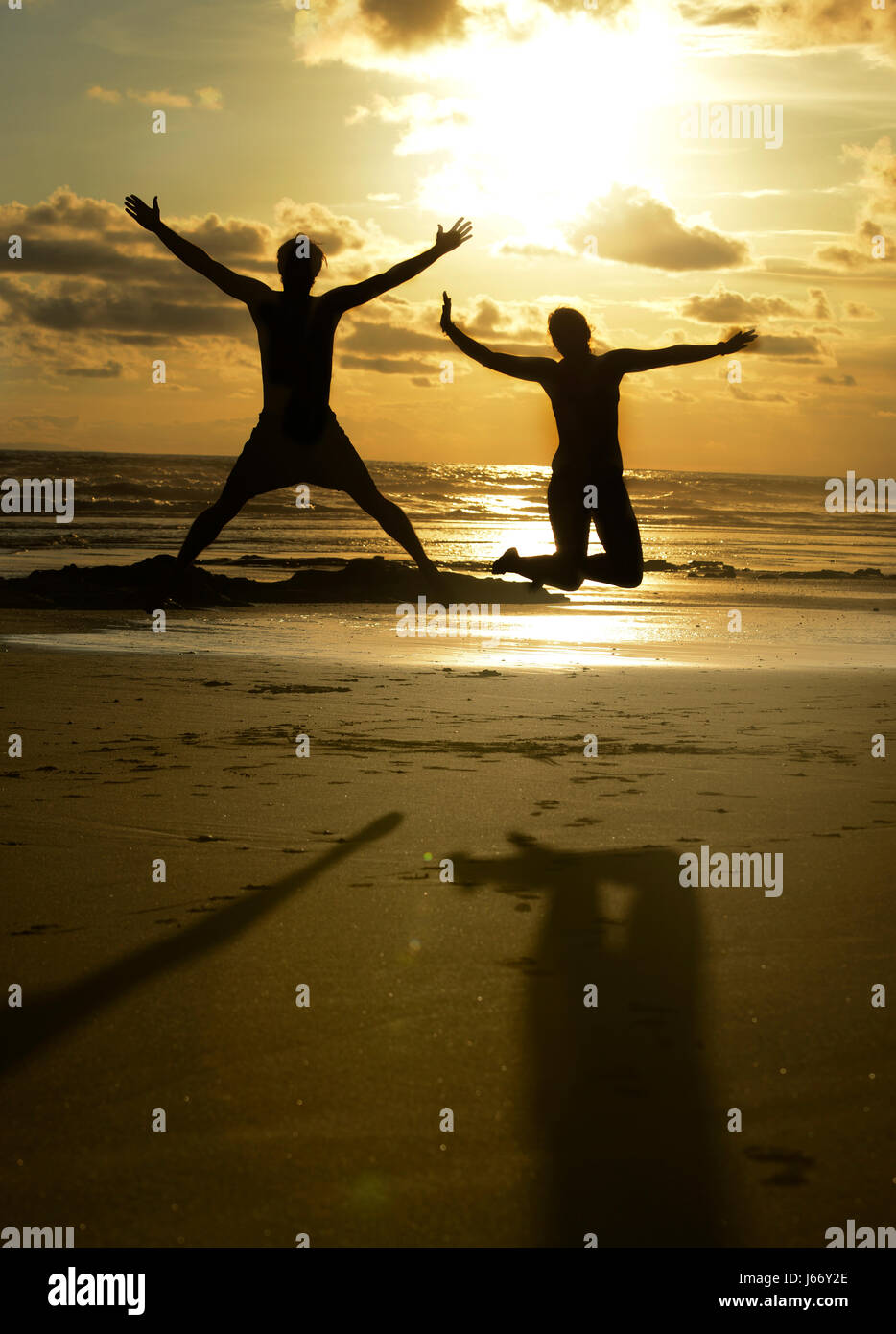 Friends jump into the air on a beach at sunset. - Stock Image