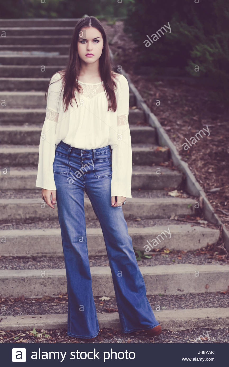 Vintage 1970's young brunette woman standing on steps - Stock Image