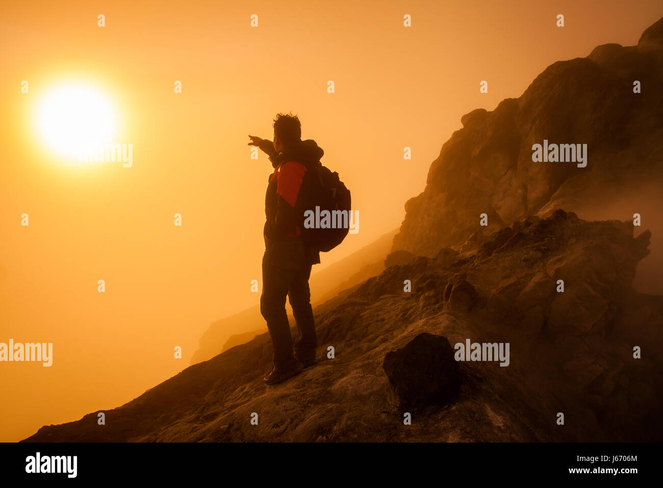 Backpacker pointing at the rising sun during sunrise over Mount Merapi (Gunung Merapi) a highly active volcano in - Stock Image