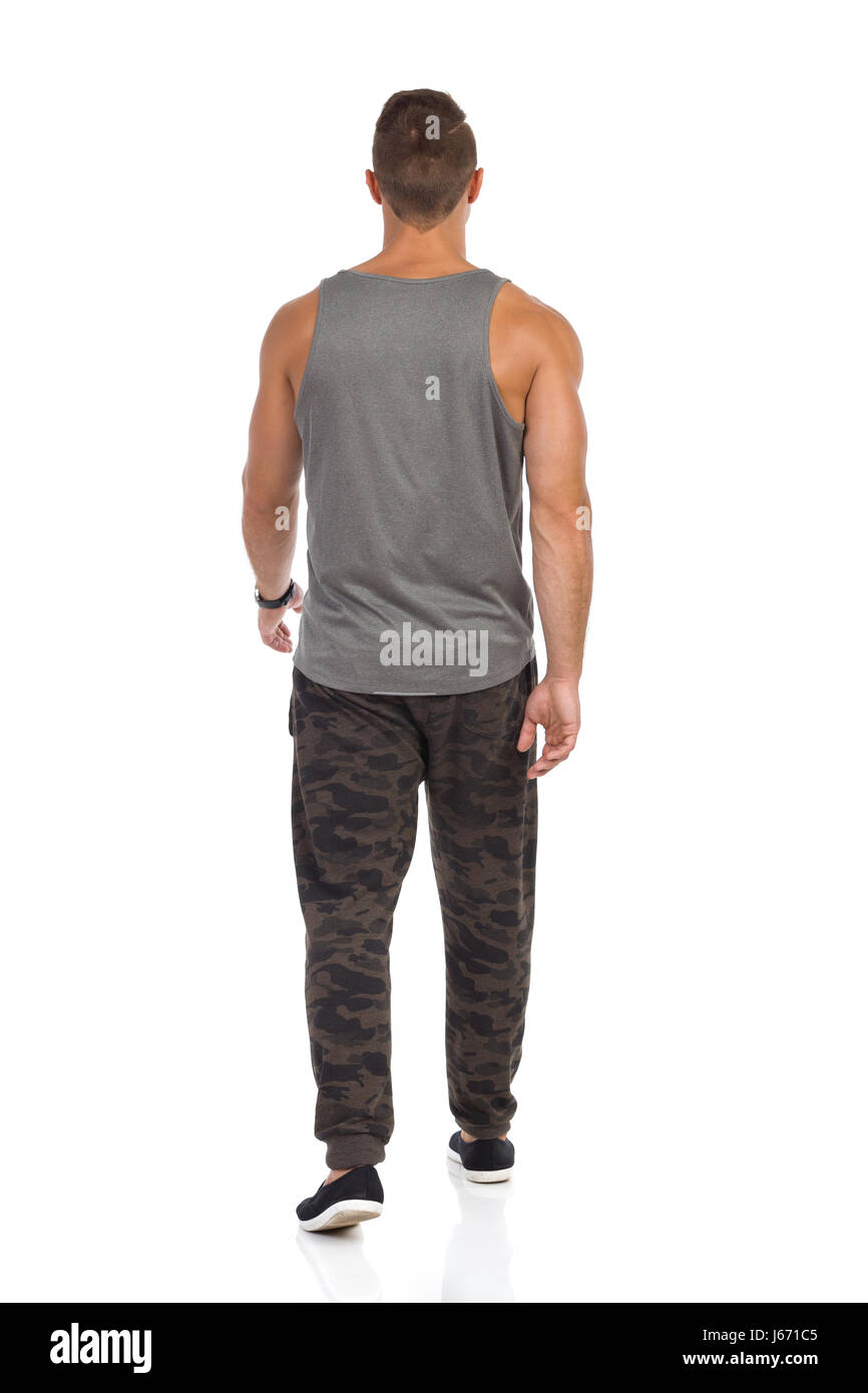 Fit man walking in tracksuit pants with camo, gray tank top and black sneakers. Rear view. Full length studio shot - Stock Image