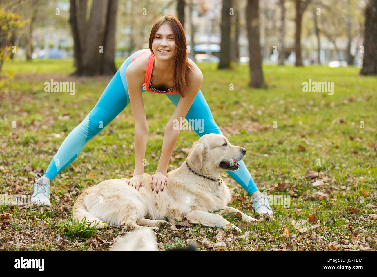 Sportswoman with labrador in park - Stock Image