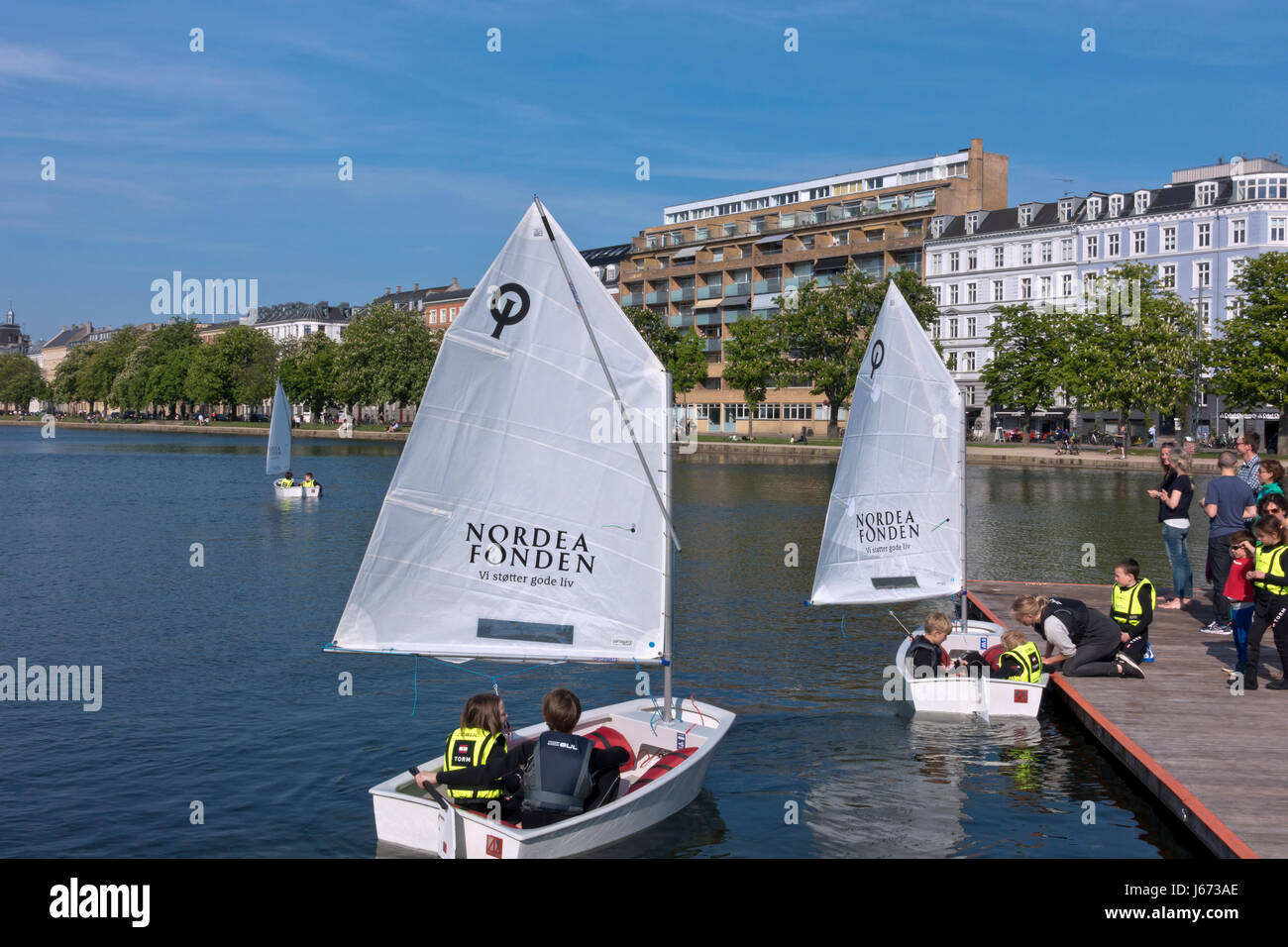 Junior sailors in optimist dinghies coached on the Peblinge Lake in central Copenhagen on a sunny afternoon in early - Stock Image