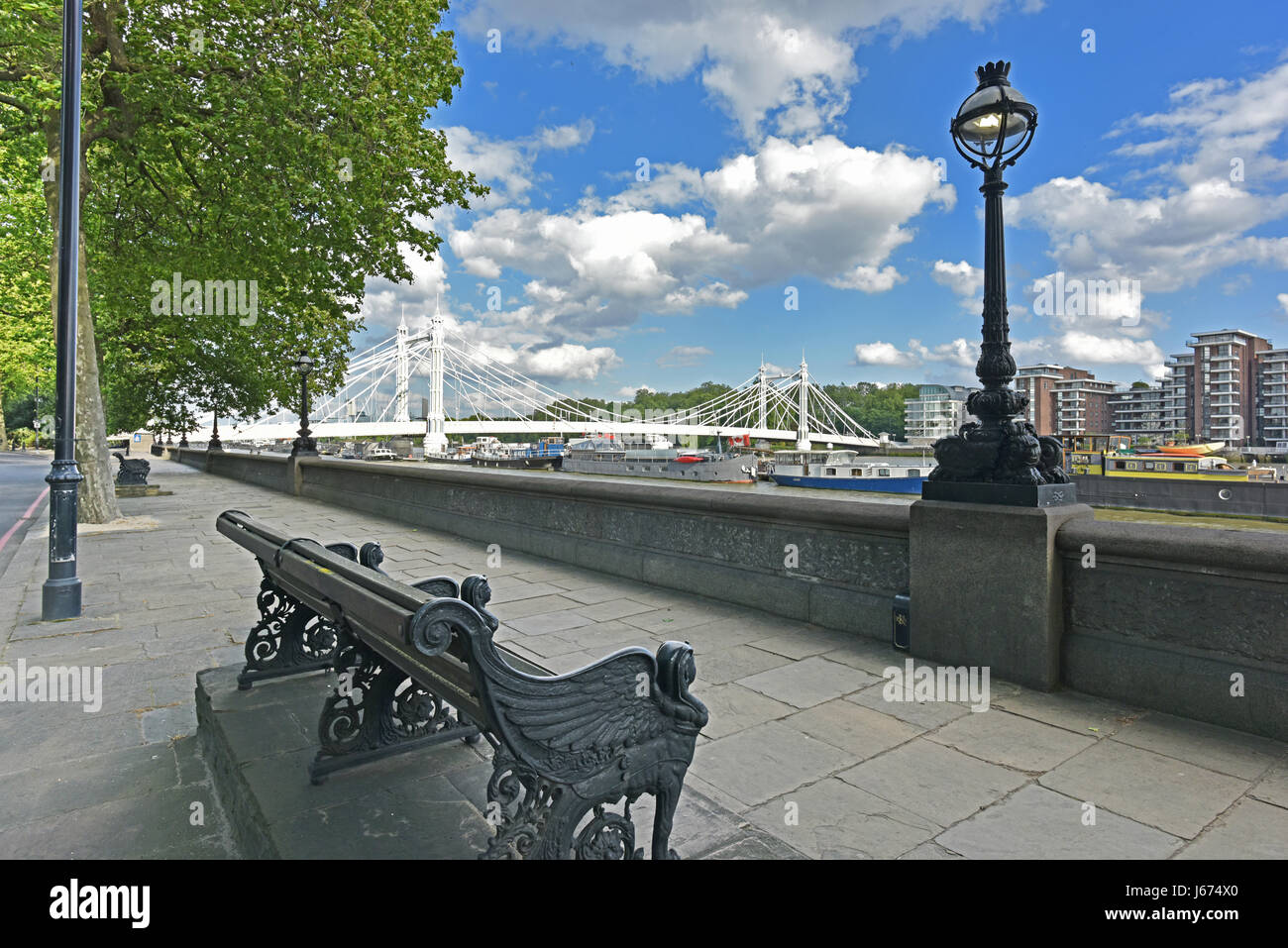 Chelsea Embankment on the River Thames and Albert Bridge with summery, blue, cloud flecked sky. - Stock Image