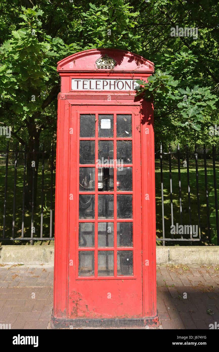 Old Red British Telephone Box on a sidewalk by Battersea Park. - Stock Image