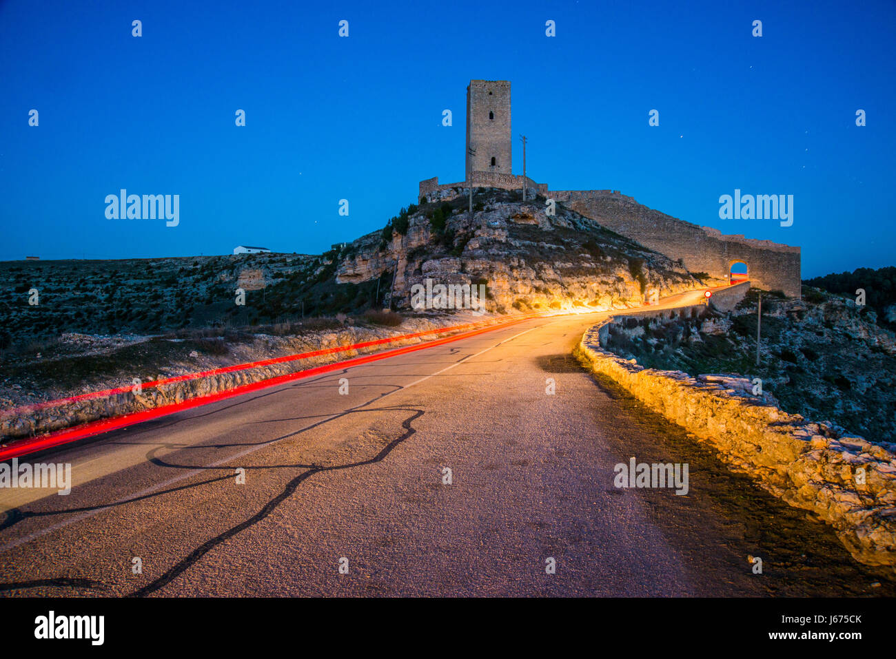 Medieval tower and light trail, night view. Alarcon, Cuenca province, Castilla La Mancha, Spain. - Stock Image