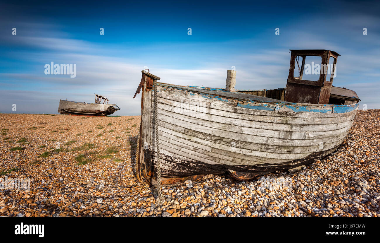 Old abandoned fishing boats on a pebble beach with long exposure clouds. Dungeness, England Stock Photo