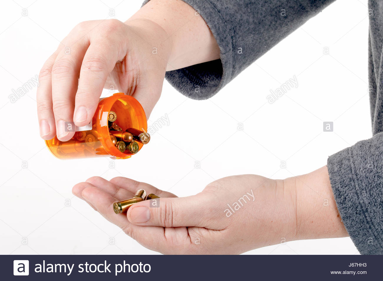 Closeup of a woman's hands holding a prescription pill bottle full of bullets tilting the bottle as if ready - Stock Image