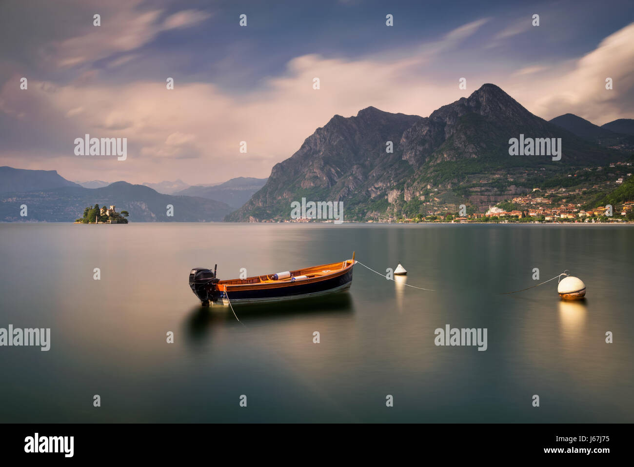 Boat on Iseo Lake with mountains in background, Italy - Stock Image