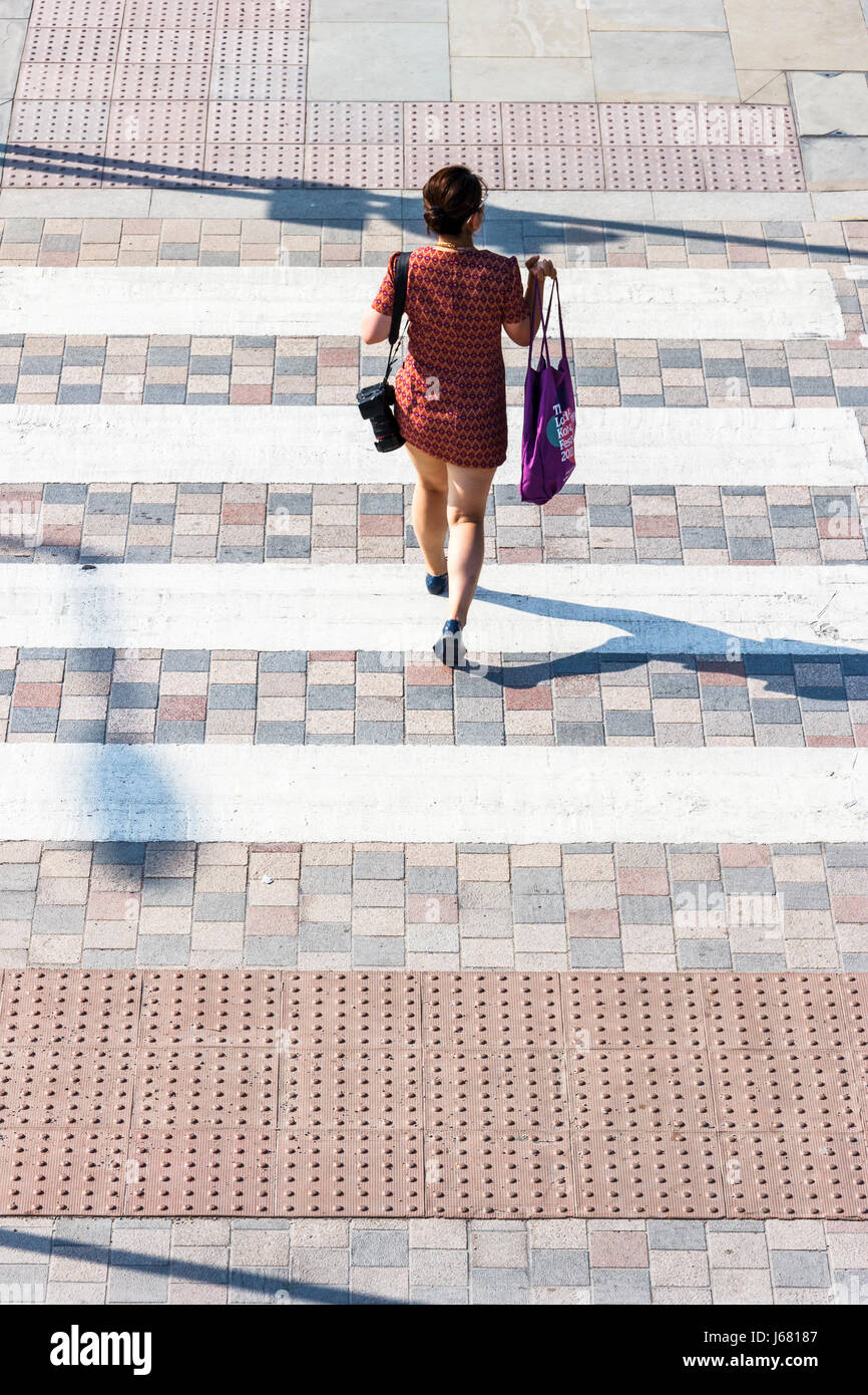 Single young female with shopping bag on a pedestrians, seen from above - Stock Image