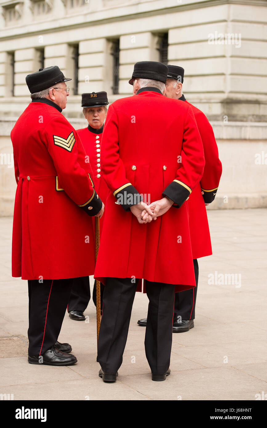 Group of ex-forces personnel known as the Chelsea Pensioners, standing in a small group talking to each other in Stock Photo