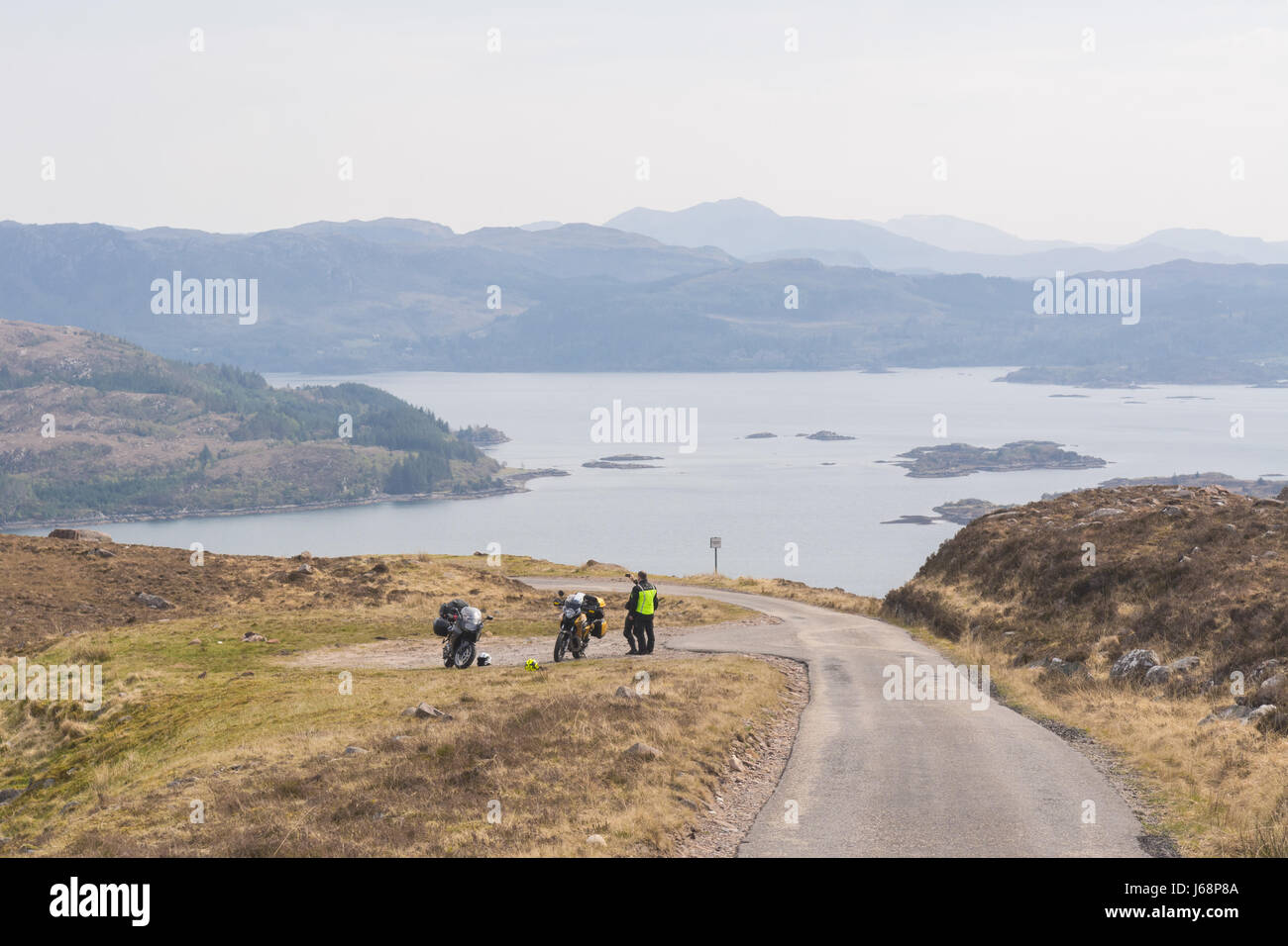 Bealach na Ba on the North Coast 500 -  two motorcyclists taking photographs of the view, Scotland, UK - Stock Image