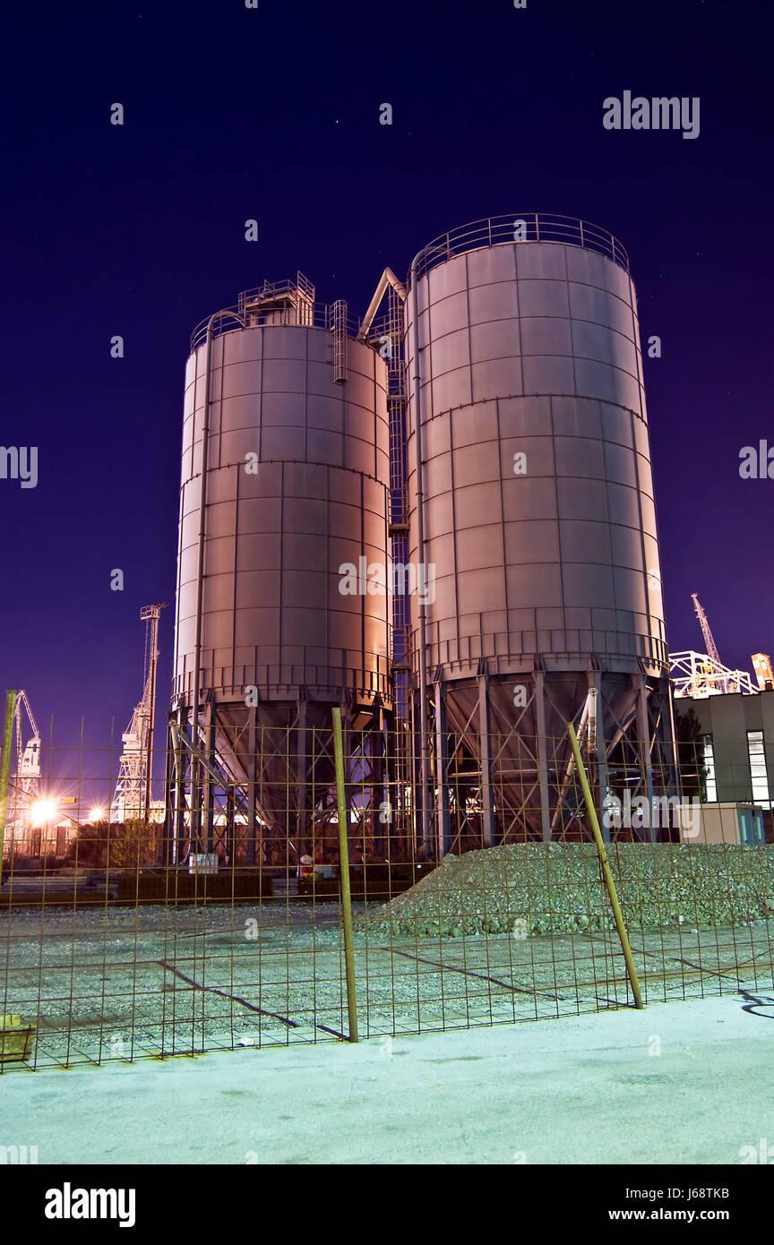 gravel storage scene location site silos construction industry night nighttime - Stock Image