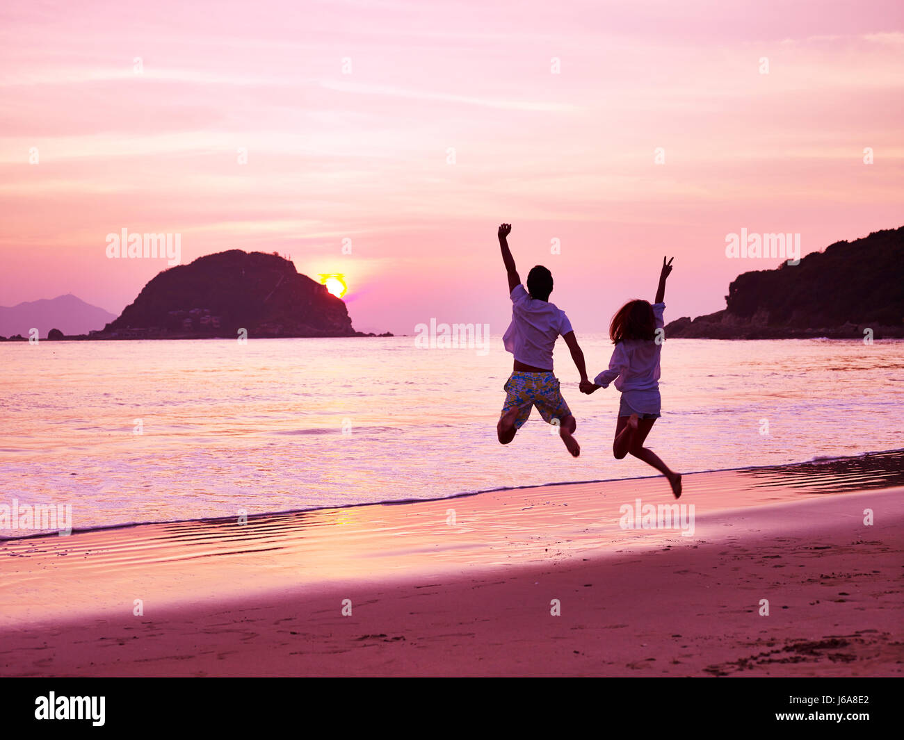 young asian couple cheering and rejoicing on beach as the sun rising. - Stock Image
