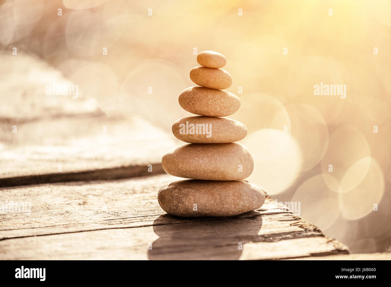 Spa stones still life on the beach, stack of pebbles on the boardwalk over sea in sunset light, peace and relaxation - Stock Image
