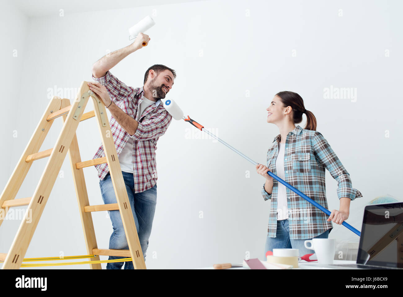 Playful Happy Couple Painting Their New House And Having Fun Together They Are Playing With Paint Rollers
