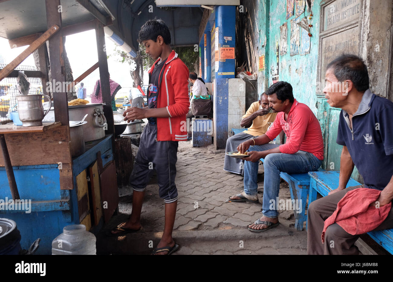 Street trader sells fast food for hungry people on the busy street in Kolkata, India on February 08, 2016. - Stock Image