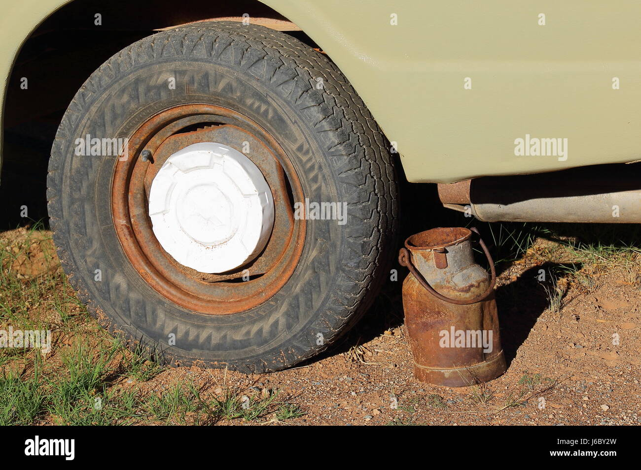 A rusted milk can next to the wheel of an old and abandoned vehicle - Stock Image