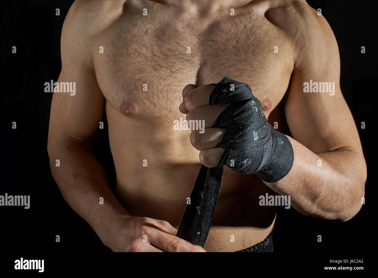 Closeup of a body combat athlet aplying tape on the hands. - Stock Image