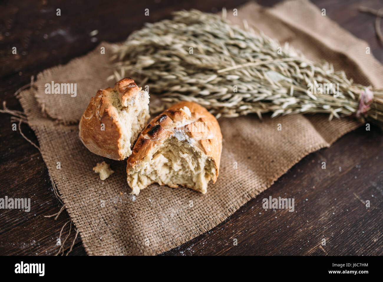 Fresh baked bread loaf with crispy crust breaked in half and wheat bunch on burlap cloth. Homemade bakery concept, - Stock Image
