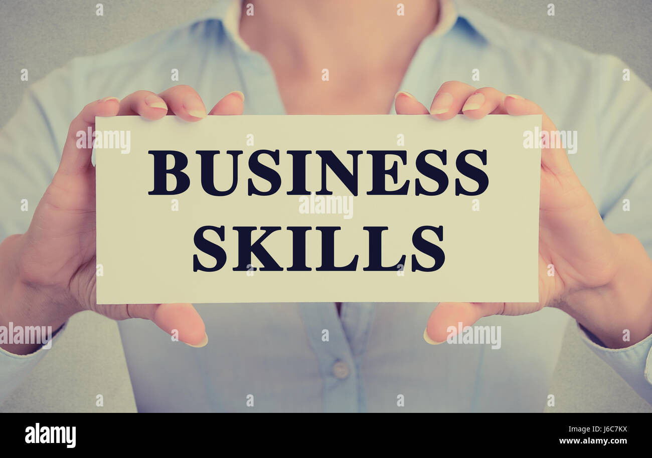 Closeup businesswoman hands holding white card sign with business skills text message isolated on grey wall office - Stock Image