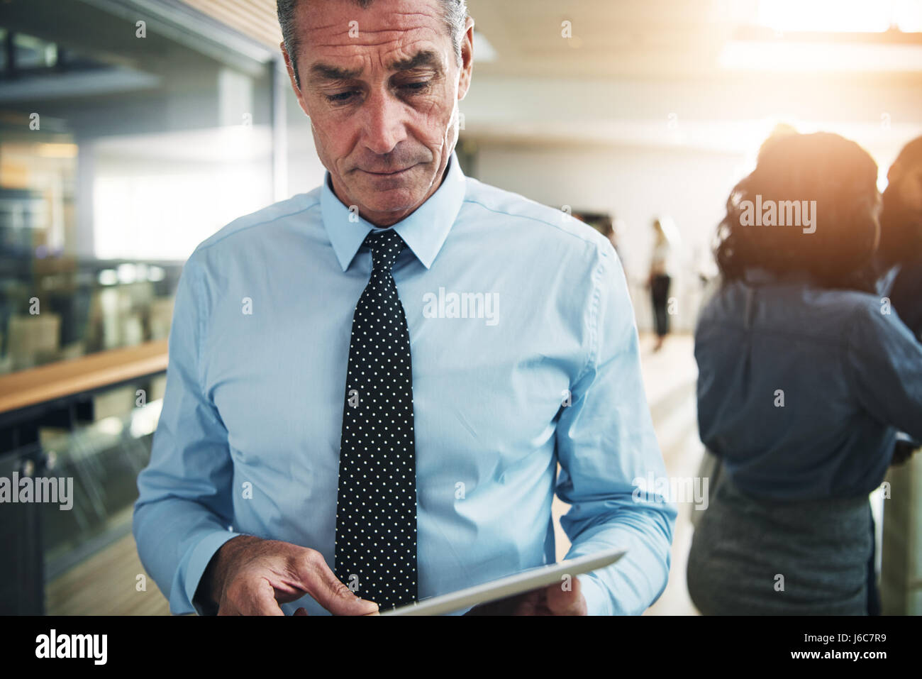 Contemporary mature pensive businessman standing and browsing tablet in office. Stock Photo