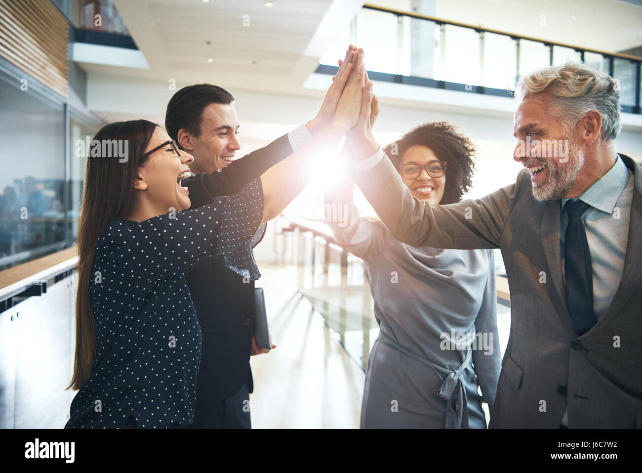 Smiling and laughing office working black and white men and women standing and giving high five to each other. - Stock Image