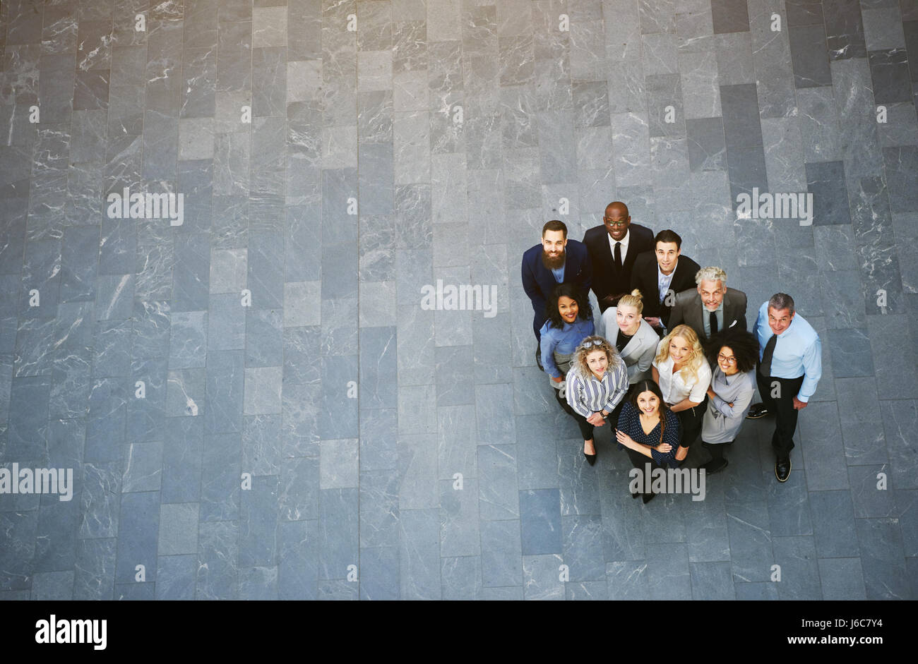 From above team of black and white men and women in formalwear standing in office hall and looking up. - Stock Image