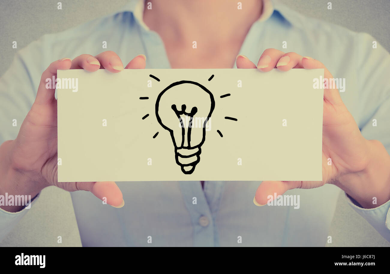 Closeup businesswoman hands holding white card sign with hand drawn illuminated light bulb isolated on grey wall - Stock Image