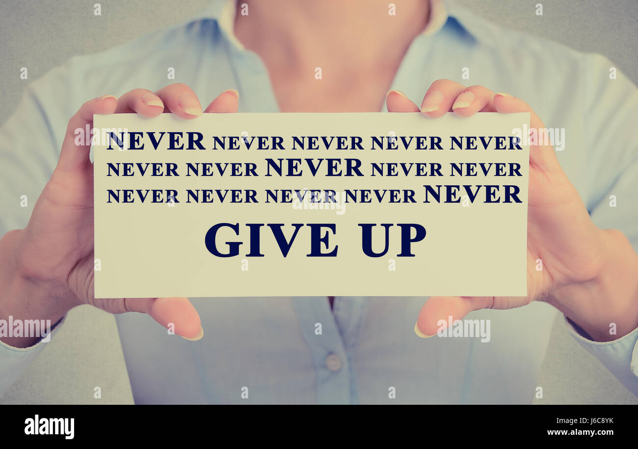 Retro Instagram vintage style image of businesswoman hands holding white card with never give up sign message isolated Stock Photo