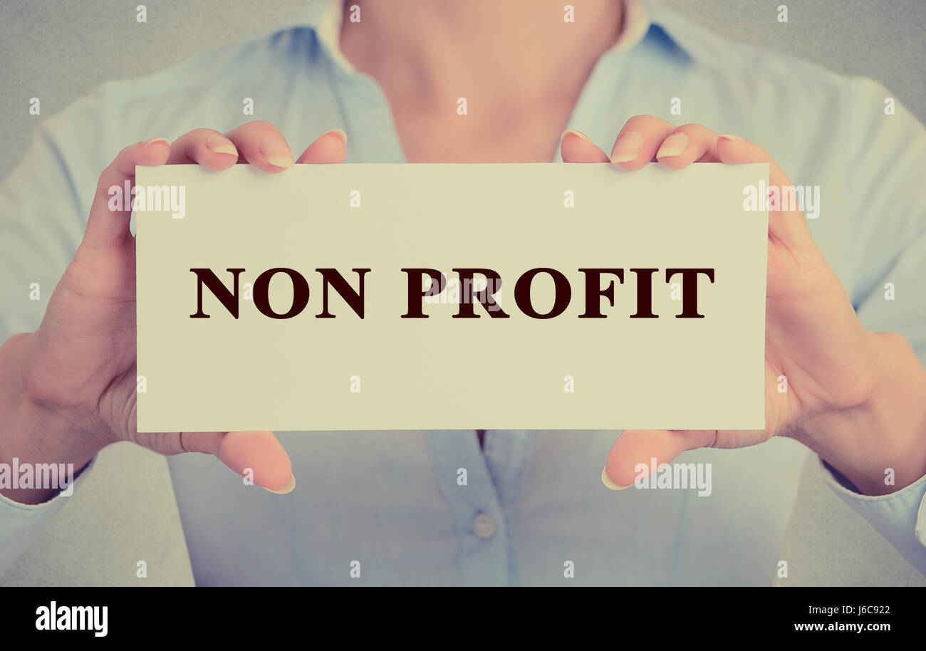 Businesswoman hands Holding Small White Sign card with Non Profit Text message - Stock Image